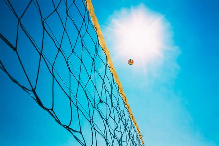 pelota de voley: Voleibol peligro en Net En El Fondo Del Cielo Azul soleado de verano. Bola de vuelo a trav�s del aire en la playa