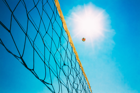 volleyball: Volleyball Ball Over Net On Background Of Blue Summer Sunny Sky. Ball Flying Through Air On Beach