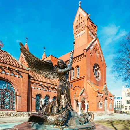 helena: Statue of Archangel Michael with outstretched wings, thrusting a spear into a dragon before the Catholic Church of St. Simon and St. Helena. Red Church on Independence Square in Minsk, Belarus