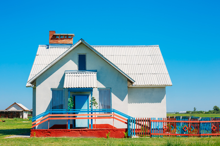 small town life: Country House With Colourful Fence. Rural Village In Summer Sunny Day Editorial