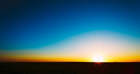 Sunset, Sunrise, Sun Over Rural Countryside Field. Bright Clear Sky And Dark Ground. Panoramic View Stock Photo