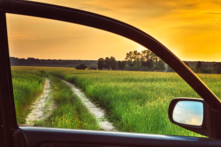 Dirty rural road in spring summer  field, meadow, countryside. View from car window. Freedom and dream concept. Stock Photo