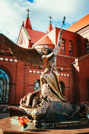 archangel: Statue of Archangel Michael with outstretched wings, thrusting spear into dragon before Catholic Church of St. Simon and St. Helena on Independence Square in Minsk, Belarus
