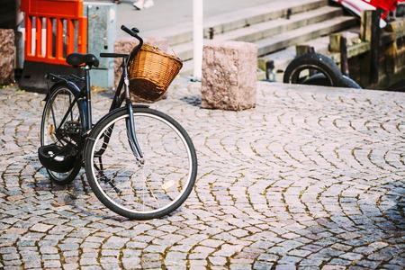bike parking: Parked Black Bicycle With Basket On Sidewalk. Bike Parking In European City. Toned Instant Filtered Photo