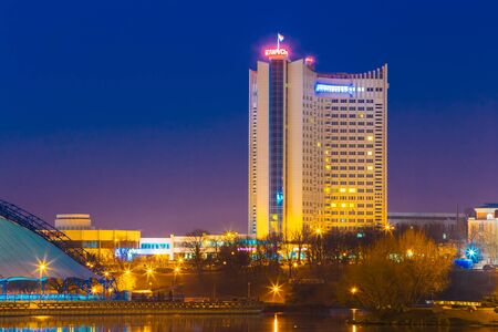 svisloch: MINSK, BELARUS - MARCH 10, 2015: Hotel Building Belarus In Old Part Minsk, Downtown Nyamiha, Nemiga View With Svisloch River, Belarus. Night Scene Street