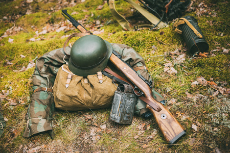 re enaction: German military ammunition of World War II on ground. Military helmet, lights, rifle Mauser Karabiner 98k