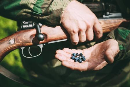 reenactor: No identificado re-enactor vestido como soldado alem�n sostiene que sostiene un rifle y moras en la mano.