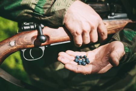 reenactmant: Unidentified re-enactor dressed as German soldier holding holding a rifle and blackberries on hand. Stock Photo
