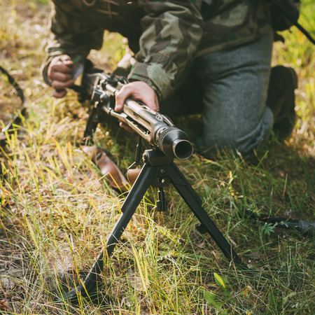 re enaction: Unidentified re-enactor dressed as German soldier machine-gunner aiming a machine gun at a enemy in summer forest Editorial
