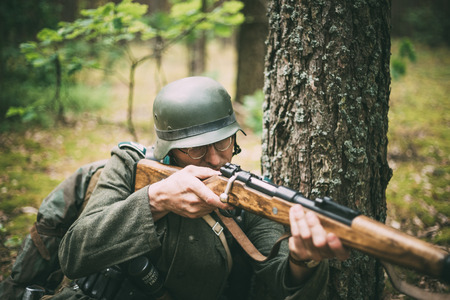 reenaction: SVETLAHORSK, BELARUS - JUNE 20, 2014: Unidentified re-enactor dressed as German soldier aiming a rifle in forest during events dedicated to 70th anniversary of Soviet offensive operation Bagration.