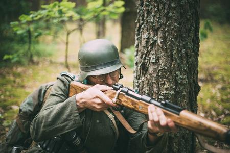 reenactor: Svetlahorsk, BIELORRUSIA - 20 de junio 2014: no identificados re-enactor vestido como soldado alem�n que apunta un rifle en el bosque durante eventos dedicados al 70 aniversario de Sovi�tica Bagration operaci�n ofensiva. Editorial