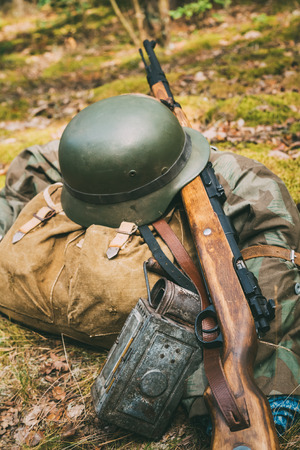 reenactmant: German military ammunition of World War II on ground. Military helmet, lights, rifle Mauser Karabiner 98k