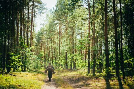 re enaction: Unidentified re-enactor dressed as German soldier during march through summer forest Stock Photo