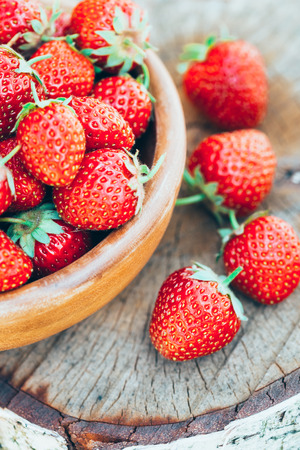 Strawberries. Organic Berries Closeup. Ripe Strawberry In The Fruit Garden, Old Wooden Bowl Filled With Succulent Juicy Fresh Ripe Red Strawberries On Old Birch Stump