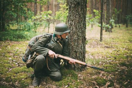 reenactor: Svetlahorsk, BIELORRUSIA - 20 de junio 2014: no identificados re-enactor vestido como soldado alem�n que apunta un rifle a un enemigo en el bosque de verano