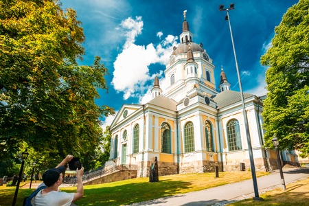 katarina: Young Man Taking Pictures Of Katarina kyrka - Church of Catherine - In Stockholm, Sweden On Mobile Device Tablet Stock Photo