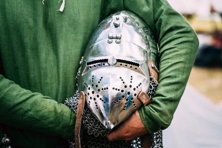 rycerz: Żelazo Helmet średniowiecznego rycerza. Kask średniowiecznych kombinezon Armour W Rękach Zdjęcie Seryjne