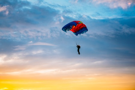 Skydiver On Colorful Parachute In Sunny Sunset Sunrise Sky. Active Hobbies