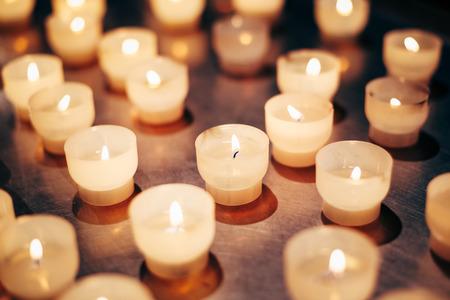 llamas de fuego: Grupo de velas en la iglesia. Las velas de luz de fondo. Llama de vela en la noche. Foto de archivo