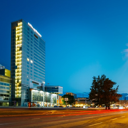 incorporates: TALLINN, ESTONIA - JULY 26, 2014: Night view of City Plaza a good example of modern office architecture that incorporates a few restaurants, a spa and a gym complex as well.