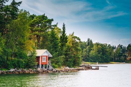 lake shore: Red Finnish Wooden Sauna Log Cabin On Island In Summer