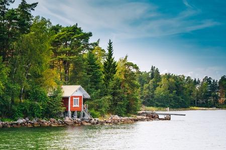 Red Finnish Wooden Sauna Log Cabin On Island In Summer