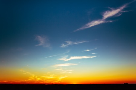dark sky: Sunset Over Rural Countryside Field. Bright Blue, Orange And Yellow Colors Sunrise Sky And Dark Ground. Stock Photo