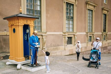 king carl xvi gustaf: STOCKHOLM, SWEDEN - JULY 30, 2014: Tourists visit and photograph the guard of honor at the Royal palace in Gamla Stan, where king Carl XVI Gustaf has his working office. Editorial