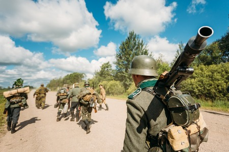 reenactmant: Unidentified re-enactors dressed as German soldiers during march through summer forest