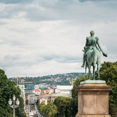 king street: OSLO, NORWAY - JULY 31, 2014: Statue of Norwegian King and main street Karl Johans Gate leading to the Royal Palace