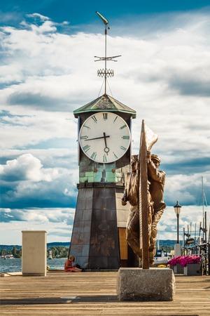 navigational light: Old Lighthouse at Aker Brygge In Oslo Embankment, Norway. Clock on Aker Brygge Dock
