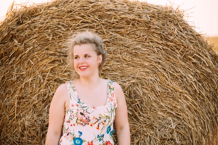 large size: Beautiful Plus Size Young Woman In Shirt Posing In Summer Field Meadow Near Hay Bales At Sunset Background