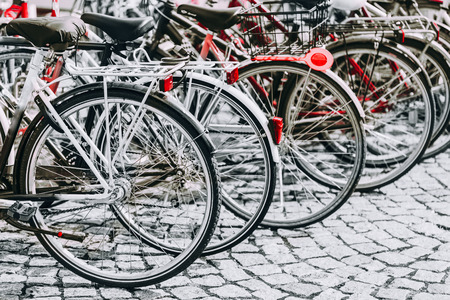 Parked Bicycles On Sidewalk. Bike Bicycle Parking In Big City. Red, Black, White and Red Colors Photo. Standard-Bild