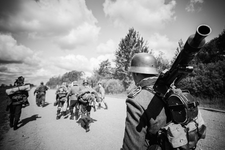 reenaction: SVETLAHORSK, BELARUS - JUNE 21, 2014: Unidentified re-enactors dressed as German soldiers during march in country road Editorial