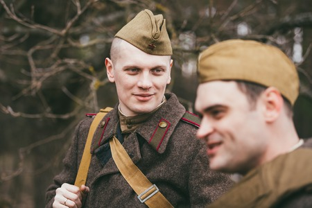 historic world event: PRIBOR, BELARUS - April, 04, 2015: Two unidentified re-enactors dressed as Soviet soldiers in overcoat during events dedicated to 70th anniversary of the Victory of the Soviet people in the Great Patriotic War. Editorial