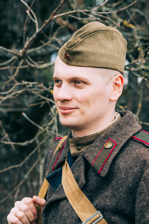 historic world event: PRIBOR, BELARUS - April, 04, 2015: Unidentified re-enactor dressed as Soviet soldier in overcoat during events dedicated to 70th anniversary of Victory of the Soviet people in the Great Patriotic War. Editorial