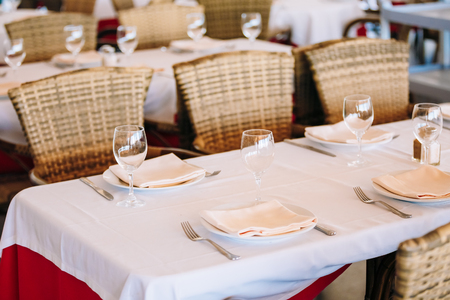 sheltered: The cozy interior of summer cafe - sheltered tables with white tablecloths and wicker chairs. European town Stock Photo