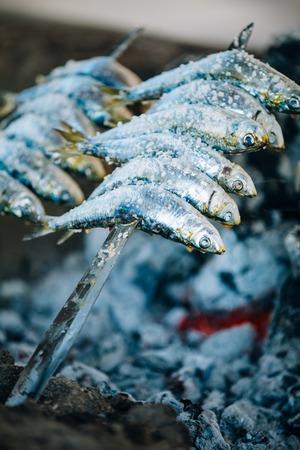 coal fish: Fish Espetos preparation. Espetos - skewer with sardines in a fire. Spanish cuisine.