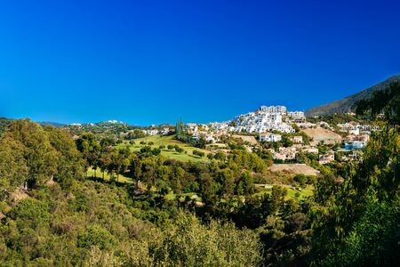spain: Panorama of Village With Whitewashed Houses In Benahavis, Malaga, Andalusia, Spain. Summer Cityscape. Sunny Day With Good Weather and Clear Blue Sky