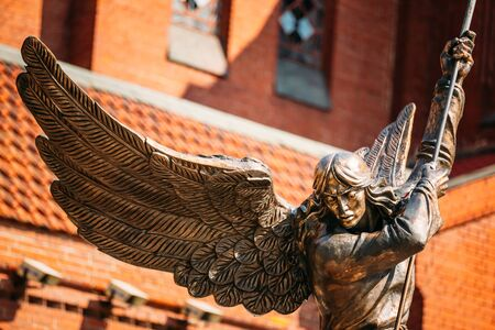 catholic angel: Statue Of Archangel Michael With Outstretched Wings, Thrusting Spear Into Dragon near Red Catholic Church Of St. Simon And St. Helena On Independence Square In Minsk, Belarus