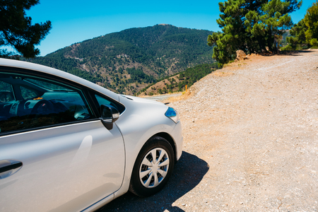 White color small hatchback car on Spainish nature landscape background. Stock Photo