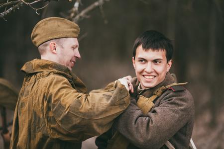 reenaction: PRIBOR, BELARUS - April, 04, 2015: Two unidentified re-enactors dressed as Soviet soldiers in overcoat