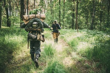reenaction: Unidentified re-enactors dressed as German soldiers running through summer forest