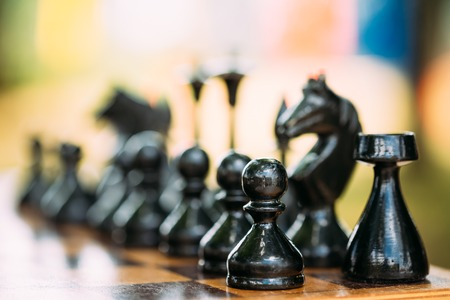 chess knight: Black Old Chess Figures Standing On Wooden Chessboard