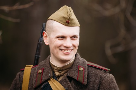 reenaction: PRIBOR, BELARUS - April, 04, 2015: Young smiling unidentified re-enactor dressed as Soviet soldier in overcoat Editorial