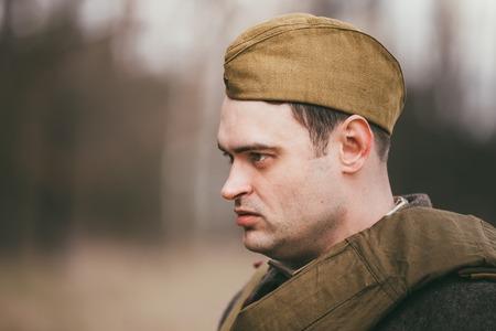 reenaction: PRIBOR, BELARUS - April, 04, 2015: Young unidentified re-enactor dressed as Soviet soldier in overcoat Editorial