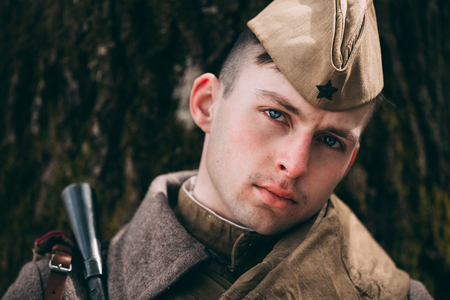 machinegun: PRIBOR, BELARUS - April, 04, 2015: Young unidentified re-enactor dressed as Soviet soldier in overcoat resting under tree Editorial