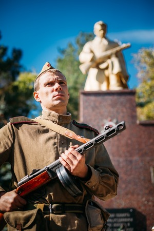 reenactor: Teryuha, Belarus - October 3, 2015: Unidentified re-enactor dressed as Soviet soldier laying of wreaths at mass grave of Soviet soldiers who died during battles for liberation of Belarus in WWII. Editorial