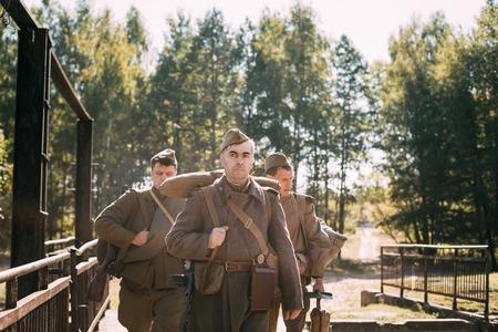 reenaction: Teryuha, Belarus - October 3, 2015: Group of unidentified re-enactors dressed as Soviet russian soldiers goes along road.