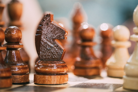 chess piece: Old Brown Chess Knight and Pawns Standing On Wooden Chessboard